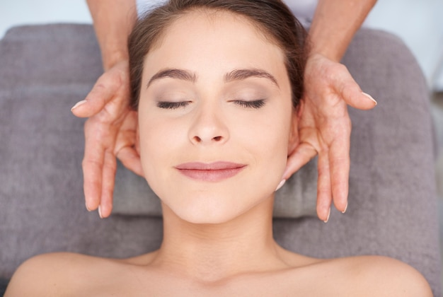 Jovem mulher recebendo massagem facial profissional Foto gratuita
