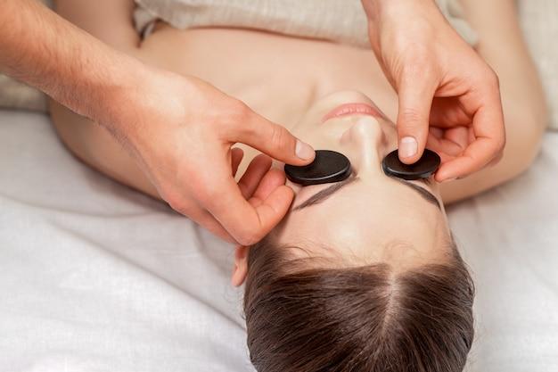 Jovem mulher recebendo massagem facial.