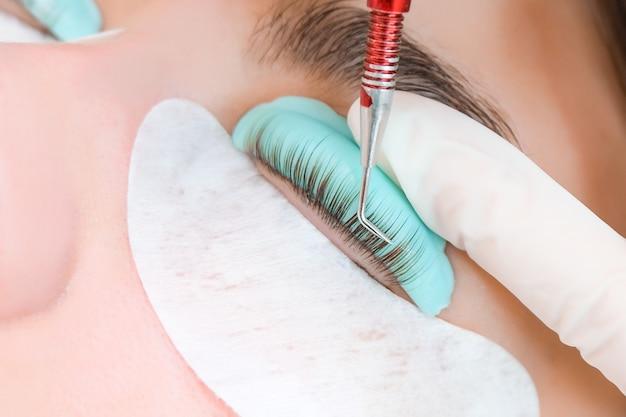 Jovem mulher recebendo procedimento de laminação de cílios em um salão de beleza, close-up