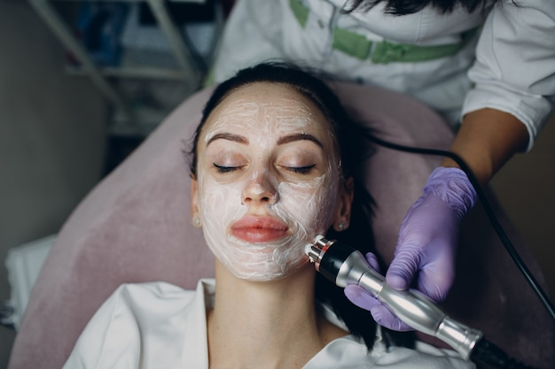 Jovem mulher recebendo rf elétrico, levantamento de massagem facial em spa de beleza com equipamento de eletroporação.