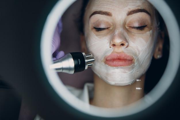 Jovem, mulher, recebendo, rf, elétrico, levantamento, facial, massagem, em, beleza, spa, com, electroporation, equipment.