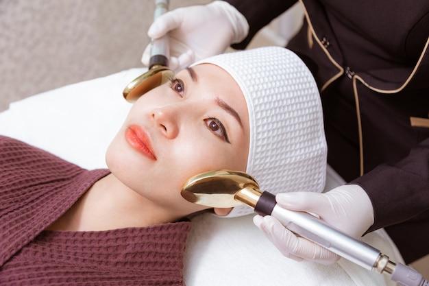 Jovem mulher recebendo seu tratamento de beleza por um médico em uma clínica de beleza