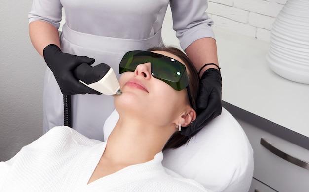 Jovem mulher recebendo tratamento a laser na clínica de cosmetologia
