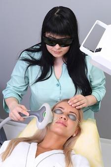 Jovem mulher recebendo tratamento de beleza facial, removendo a pigmentação na clínica cosmética.