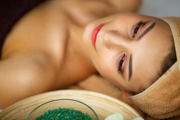 Jovem mulher recebendo tratamento de spa no salão de beleza