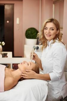 Jovem mulher recebendo tratamento facial a laser na clínica de cosmetologia. salão de beleza e spa