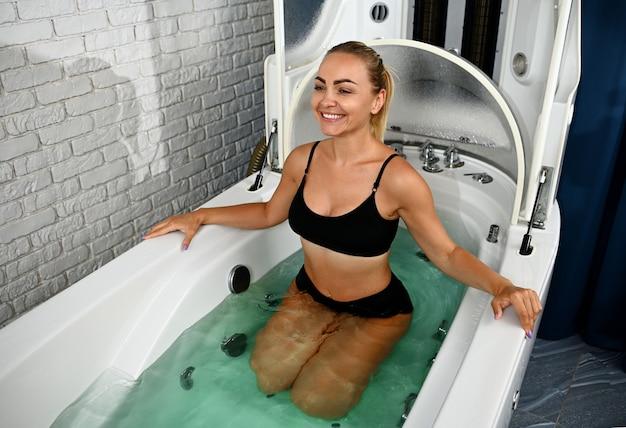 Jovem mulher recebendo tratamentos e procedimentos médicos e de bem-estar em uma cápsula de bem-estar spa.