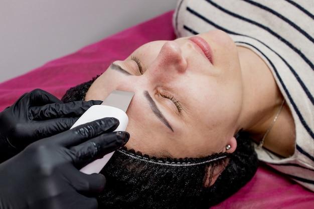 Jovem mulher recebendo ultra-som cavitação facial peeling de limpeza. limpeza de tratamento de cuidados da pele facial cosmetologia.
