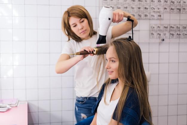 Jovem mulher recebendo um novo penteado com secador no salão de estilo de cabelo profissional.
