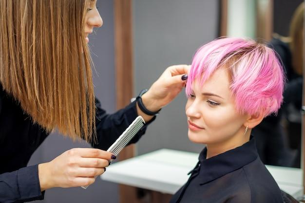 Jovem mulher recebendo um penteado curto rosa por uma cabeleireira em um salão de beleza