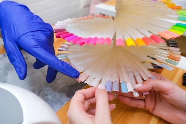 Jovem mulher recebendo um serviço de manicure em um salão de beleza. paleta de cores de verniz
