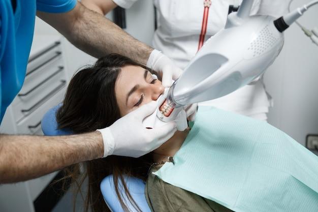 Jovem mulher recebendo um tratamento de clareamento dos dentes em um dentista.