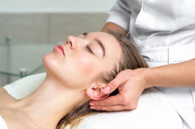 Jovem mulher recebendo uma massagem na cabeça.