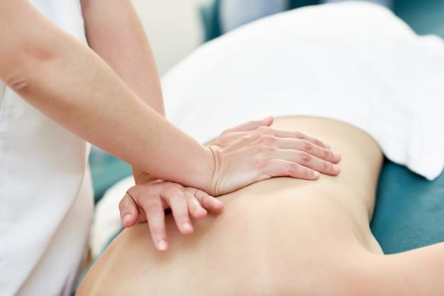 Jovem mulher recebendo uma massagem nas costas por terapeuta profissional.