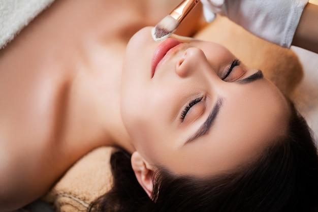 Jovem mulher relaxa durante tratamentos de spa no estúdio de beleza
