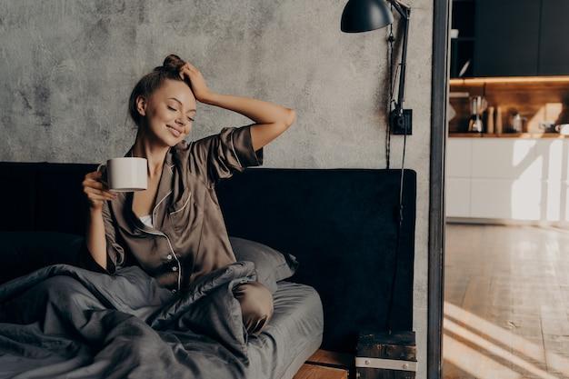 Jovem mulher relaxada em um terno elegante de casa acordando com uma xícara de café na cama em um quarto aconchegante e elegante em casa, estendendo-se da noite de sono e aproveitando o tempo de lazer matinal e o sol da janela