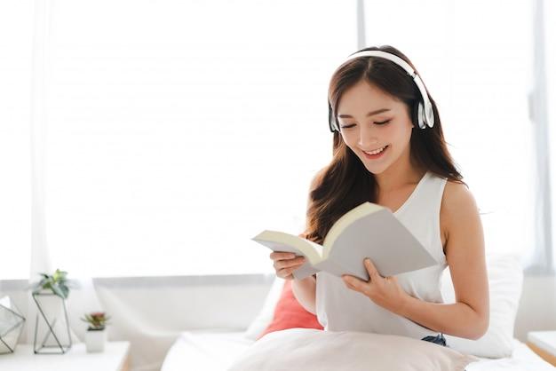 Jovem mulher relaxando e lendo o livro na cama em casa