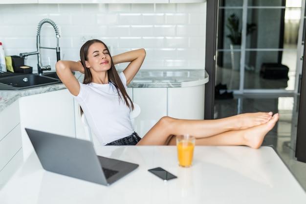 Jovem mulher relaxando em sua cozinha, inclinando-se para trás em uma cadeira com as mãos atrás do pescoço e os olhos fechados na frente de um laptop