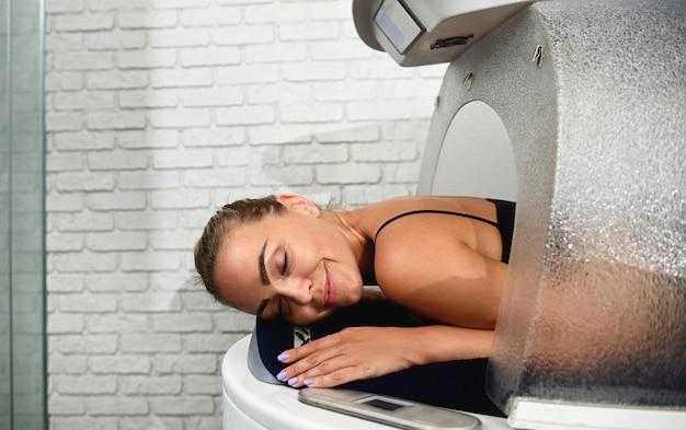 Jovem mulher relaxando enquanto recebe um tratamento de cápsula de spa de bem-estar em uma clínica de spa moderna. fechar-se