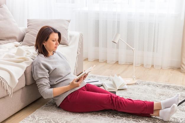 Jovem mulher relaxando no chão em casa lendo livro