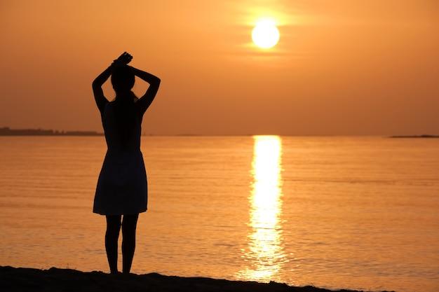 Jovem mulher relaxando sozinho na costa de areia do oceano à beira-mar, desfrutando de uma noite tropical quente.