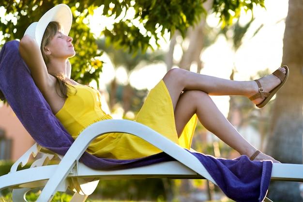 Jovem mulher relaxante ao ar livre num dia ensolarado de verão. senhora feliz, deitado na cadeira de praia confortável, sonhando acordado. calma linda garota sorridente, desfrutando de ar fresco relaxante com os olhos fechados.