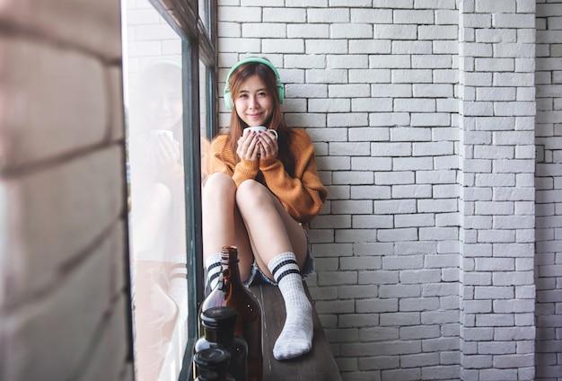 Jovem mulher relaxante com música de fone de ouvido na janela perto de casa aconchegante