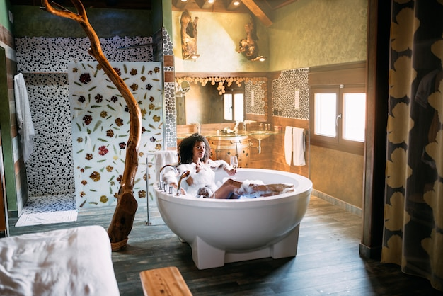 Jovem mulher relaxante no banho de hidromassagem coberto de espuma