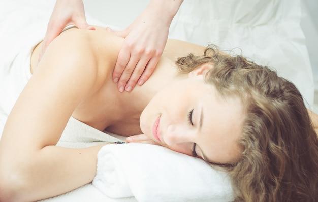 Jovem mulher relaxar e desfrutar de massagens em um salão