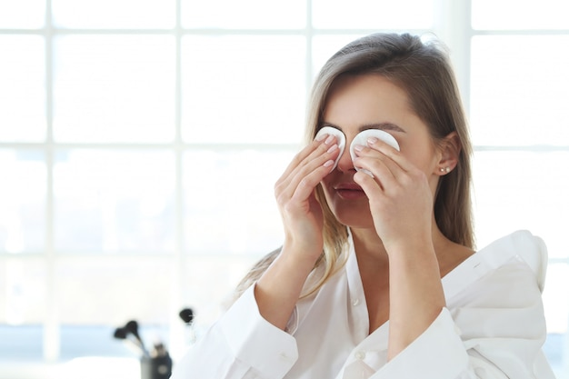Jovem mulher remover maquiagem facial com toalhitas de removedor de maquiagem.