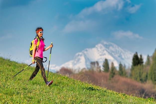 Jovem mulher retornando de uma excursão a pé nórdico nas montanhas na primavera