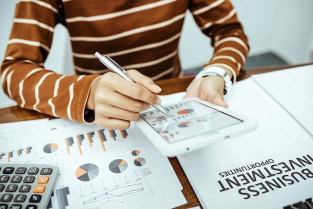 Jovem mulher rever dados despesas domésticas e gráficos de negócios na sala.