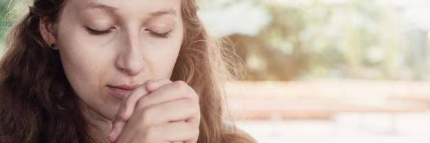 Jovem mulher rezando com os olhos fechados
