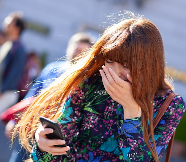 Jovem mulher ri olhando para celular