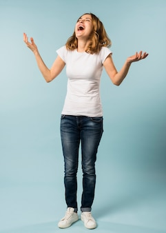 Jovem mulher rindo alto contra o fundo azul