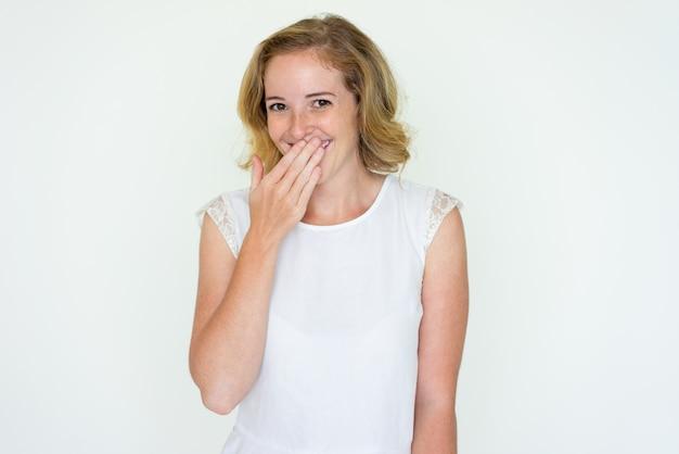 Jovem mulher rindo e cobrindo a boca com a mão