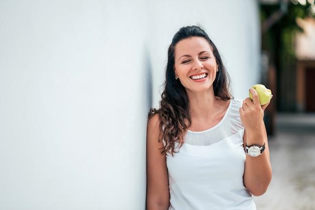 Jovem mulher rindo e comendo uma maçã ao ar livre.