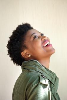 Jovem mulher rindo e olhando para cima