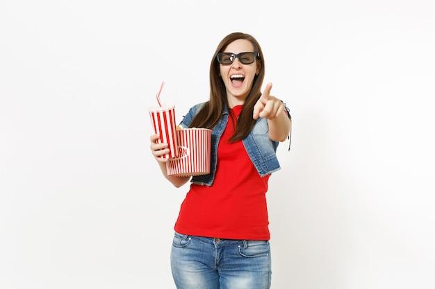 Jovem mulher rindo em óculos 3d, assistindo a um filme, segurando um balde de pipoca e um copo plástico de refrigerante ou coca-cola, apontando o dedo indicador na câmera, isolado no fundo branco. emoções no cinema.