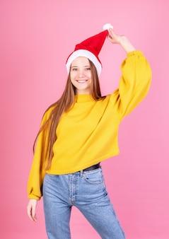 Jovem mulher rindo no chapéu de papai noel e camisola amarela em fundo rosa