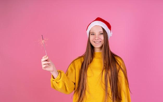 Jovem mulher rindo no chapéu de papai noel e camisola amarela segurando um diamante no fundo rosa