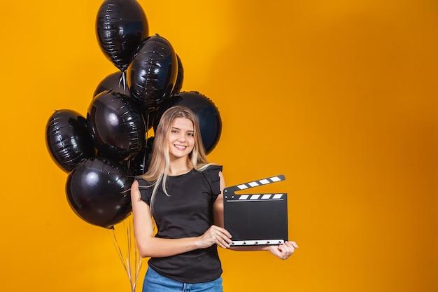 Jovem mulher rindo segurando filme preto clássico fazendo claquete e comemorando com balões de ar preto isolados sobre fundo amarelo. festa de aniversário, conceito de emoções de pessoas.