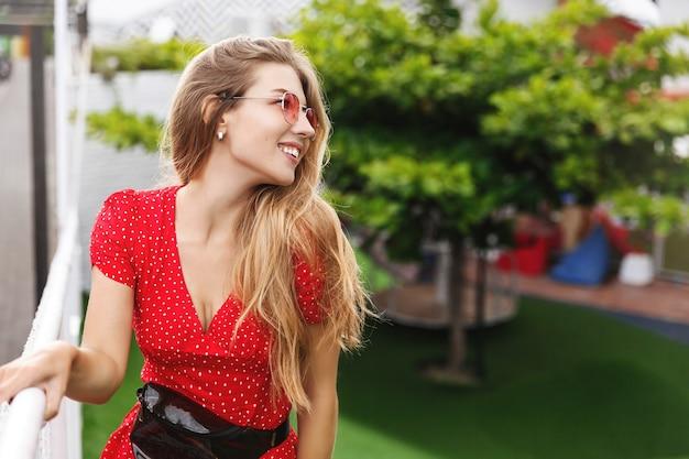 Jovem mulher romântica apreciando a paisagem de um resort tropical, em pé no parque e sorrindo