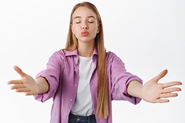 Jovem mulher romântica fecha os olhos, beija e se abraça com os braços estendidos, em pé contra uma parede branca