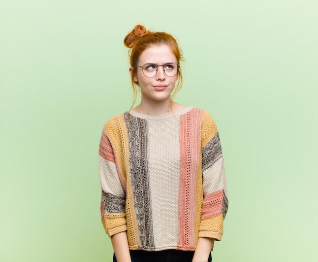 Jovem mulher ruiva bonita olhando confusa e confusa, pensando ou tentando resolver um problema ou pensando contra a parede verde