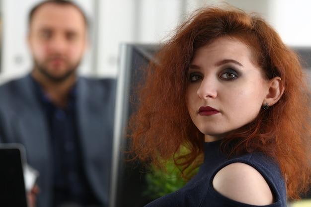 Jovem mulher ruiva bonita sentar à mesa no escritório, no gabinete de seu chefe