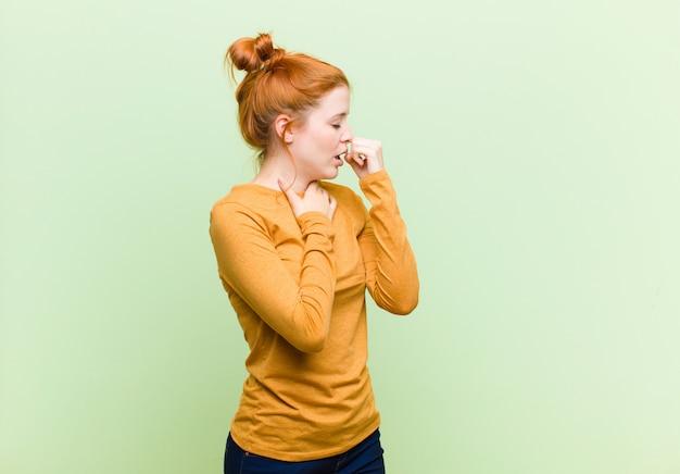 Jovem mulher ruiva bonita sentindo-se mal com sintomas de dor de garganta e gripe, tossindo com a boca coberta contra a parede verde