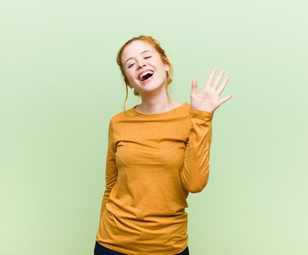 Jovem mulher ruiva bonita sorrindo alegremente e alegremente, acenando com a mão, dando as boas-vindas e cumprimentando-o ou dizendo adeus ao longo da parede verde