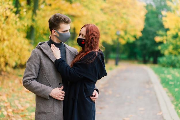 Jovem mulher ruiva coloca uma máscara facial enquanto caminhava com o jovem no parque outono.