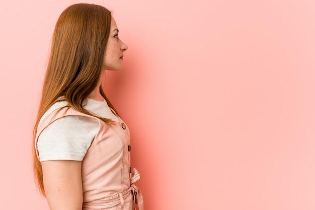 Jovem mulher ruiva com sardas olhando para a esquerda, pose de lado.